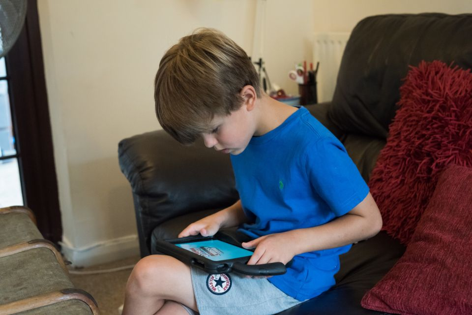 Autistic boy sat looking at an app on a tablet.